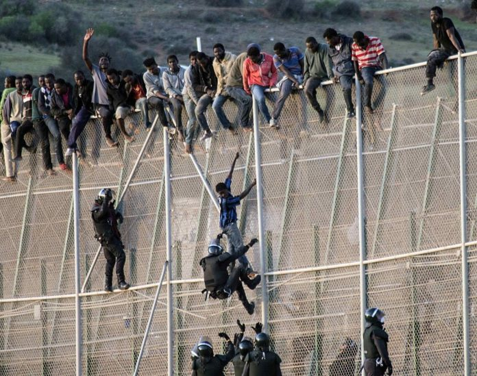 Migrants climb the fence on the border between Melilla and-Morocco